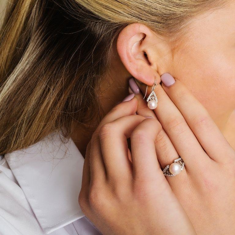 Intricate Trinity Knot Pearl Earrings on Model
