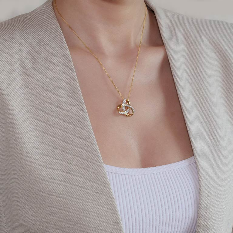 14KT Gold Vermei Trinity Knot Necklace studded with Cubic Zirconias On Model
